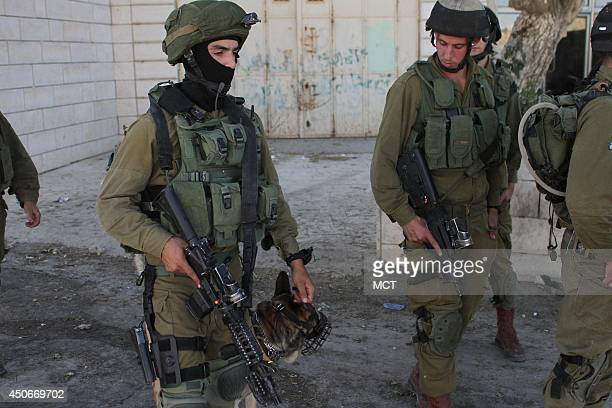 Israeli infantry soldiers get ready to star a search operation in the West Bank village of Beit Einun near Hebron on June 15 as part of the search...