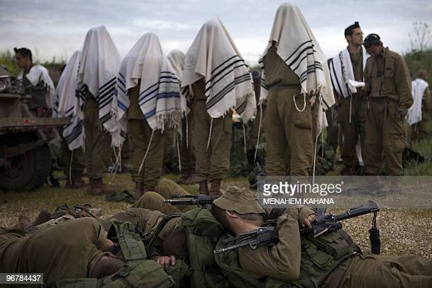 Israeli infantry soldiers of the army's Kfir brigade wrapped with Jewish prayer shawls pray early in the morning as other comrades rest following an...