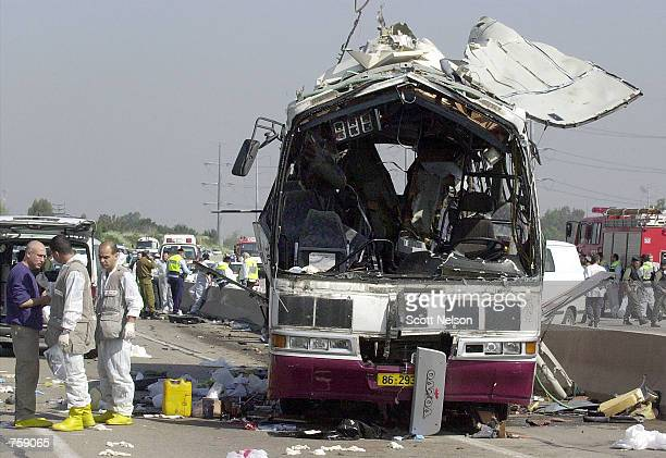 Israeli investigators examine the site of a Palestinian suicide bus bombing that killed at least eight people April 10 2002 outside the Northern...
