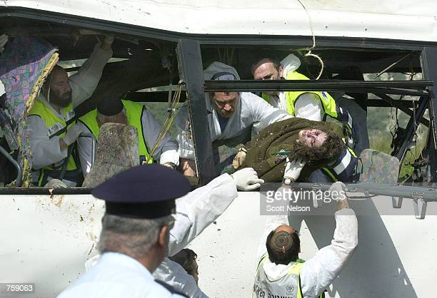 Israeli investigators remove a corpse from the site of a Palestinian suicide bus bombing that killed at least eight people April 10 2002 outside the...