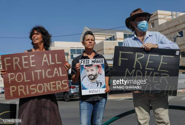 Israeli left-wing activists lift placards during a demonstration calling for the release of Palestinian administrative detainees, including Maher...