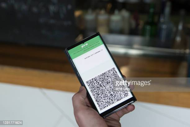 Israeli man holds his smart phone as he is presenting a 'Covid19' vaccination certificate named 'Green Pass', before entering a coffee shop on March...