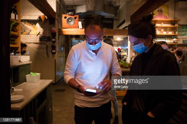 Israeli man holds his smart phone as he is presenting a 'Covid19' vaccination certificate named 'Green Pass', before entering a restaurante on March...