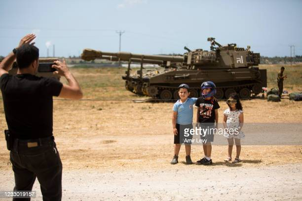 Israeli man takes a photo of his kids near Israeli tanks after Israel and Hamas agreed on a ceasefire on May 21, 2021 in Sderot, Israel. Yesterday,...