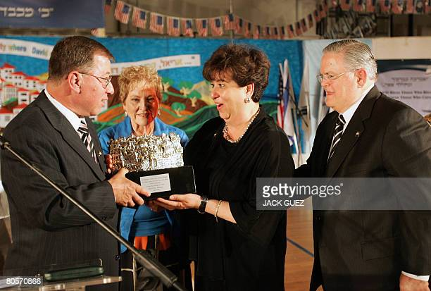 Israeli mayor of Ariel Ron Nachman gives a gift to US pastor John Hagee and his wife Diana during a welcoming ceremony at Ariel settlement in the...