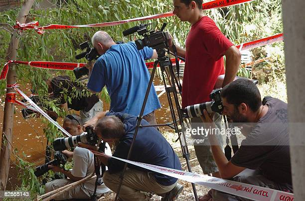 Israeli media work from behind a cordoned section on the highly polluted Yarkon river during police searches for the body of fouryearold...