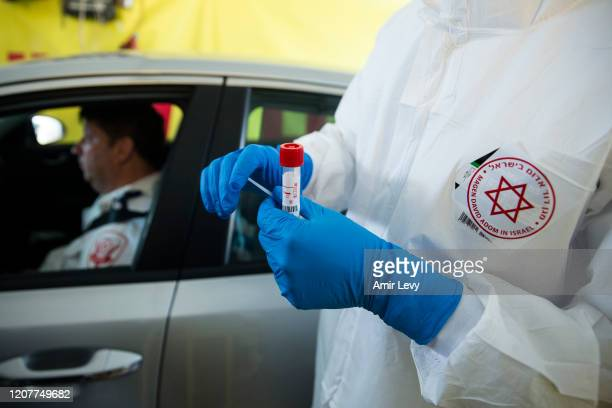 Israeli medical worker holds a swab test for coronavirus at a drive-through site during a presntation for the press before opening on March 20, 2020...