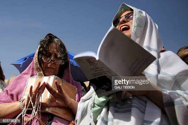 Israeli members of the liberal Jewish religious group Women of the Wall wear 'Tallit' traditional Jewish prayer shawls for men as one gestures with...