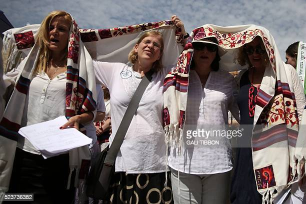 Israeli members of the liberal Jewish religious group Women of the Wall spread open their 'Tallit' traditional Jewish prayer shawls for men as...