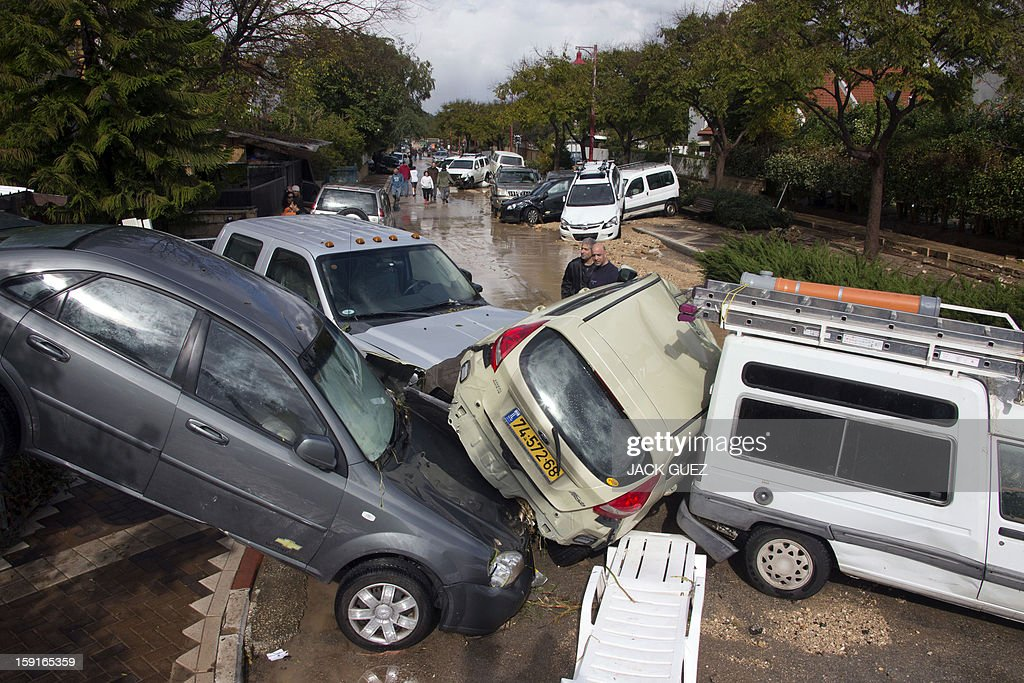 Israeli men look at the damaged cars in Beit Hefer near the Meditrranean coastal city of Netanya, north of Tel Aviv, on January 9, 2013, after heavy rains overnight. Israel and the Palestinian territories have been lashed by heavy rain and high winds since January 6, which has caused flooding across the region.