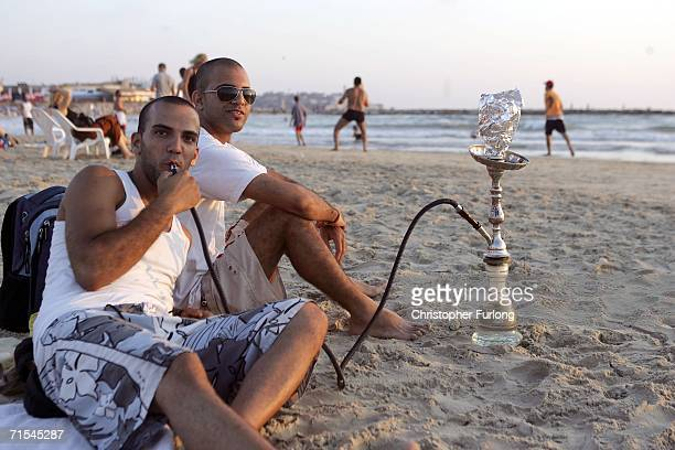 Israeli men smoke a water pipe on the main beach of Tel Aviv as fighting and rocket attacks continue on the north border and in southern Lebanon July...