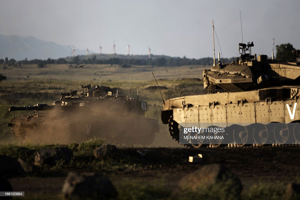Israeli Merkava tanks maneuver during a drill in the Israeli annexed Golan Heights near the border with Syria on May 5, 2013. Israel carried out a pre-dawn air strike near Damascus, targeting Iranian missiles destined for Lebanon's Hezbollah in the second such raid on Syria in three days, a senior Israeli source said.