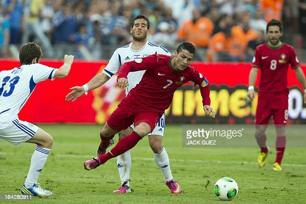 Israeli midfielder Gal alberman is challenged by Portuguese forward Cristiano Ronaldo during the FIFA 2014 World Cup European zone qualifying group F...