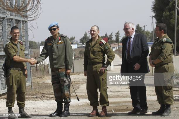 Israeli military and UN peacekeepers are pictured during the reopening of the only crossing point between Syria and Israeliannexed Golan heights near...