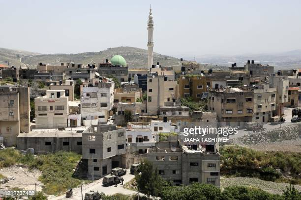 Israeli military vehicles are pictured in the village of Yabad near the West Bank city of Jenin on May 12 during a search operation after the...