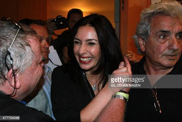 Israeli Minister of Sports and Culture Miri Regev shakes hands with a man upon arriving to theatre awards ceremony in Tel Aviv on June 19 2015 Regev...