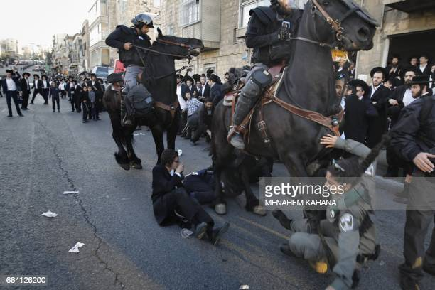 TOPSHOT Israeli mounted policemen run over a police woman as he disperses ultraOrthodox Jews during a protest against Israeli army conscription in...