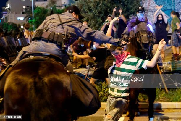 Israeli mounted policemen try to disperse protesters during a demonstration against the Israeli prime minister and against the second nationwide...