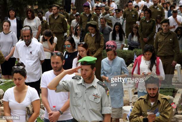 Israeli mourners observe two minutes of silence near graves during a ceremony at the Mount Herzel military cemetery in Jerusalem as they mark...