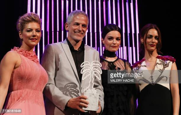 Israeli movie producer film director and actor Reshef Levi celebrates on stage after receiving the trophy for best performance award next to members...