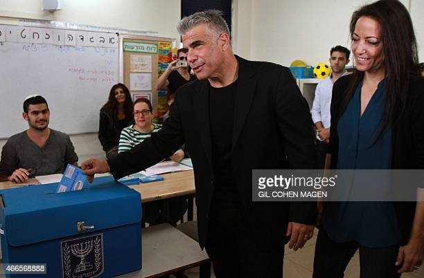 Israeli MP and chairperson of centerright Yesh Atid party Yair Lapid casts his ballot at a polling station with his wife Lihi on March 17 2015 in Tel...