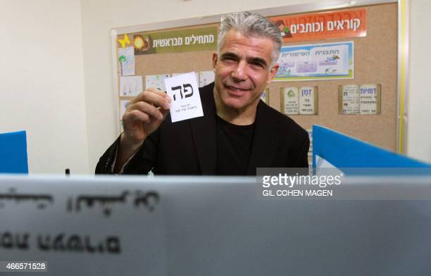 Israeli MP and chairperson of centerright Yesh Atid party Yair Lapid prepares to cast his ballot at a polling station on March 17 2015 in Tel Aviv...