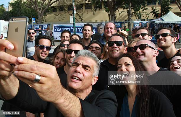 Israeli MP and chairperson of centerright Yesh Atid party Yair Lapid takes a selfie with his wife Lihi and his supporters outside a polling station...
