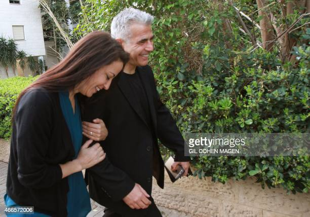 Israeli MP and chairperson of centerright Yesh Atid party Yair Lapid walks with his wife Lihi after voting at a polling station on March 17 2015 in...