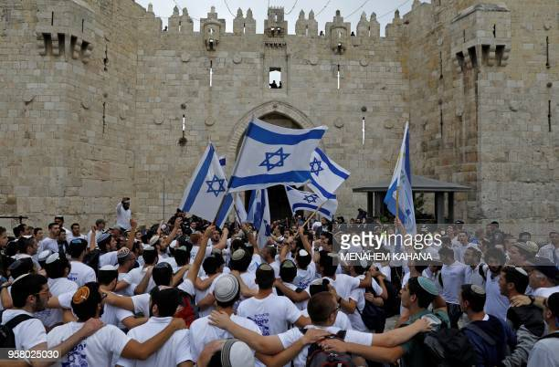 TOPSHOT Israeli nationalist settlers wave their national flag as they celebrate the Jerusalem Day at the Old City's Damascus gate in Jerusalem on May...