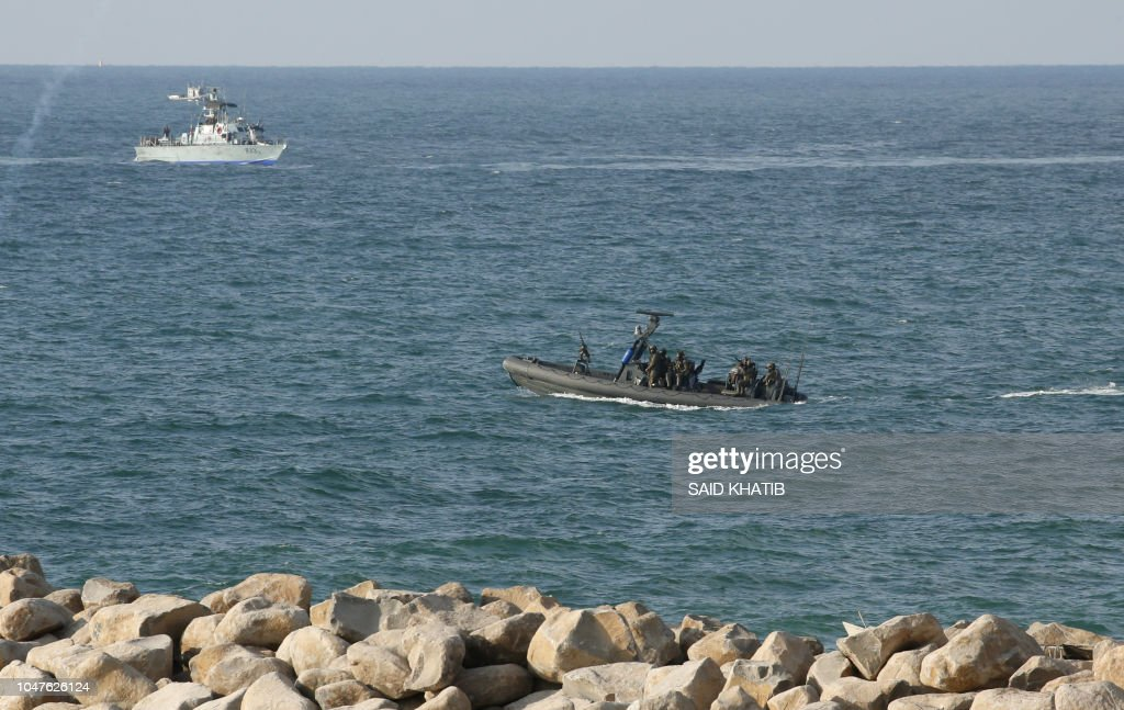 Israeli navy personnel keep watch from boats as Palestinian