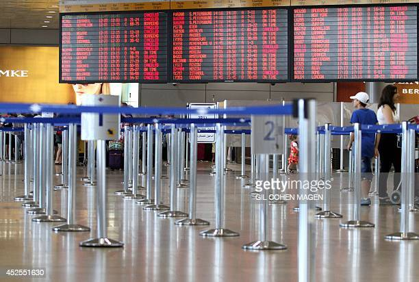 Israeli passengers walk near a departure time flight board displaying various cancellations at Ben Gurion International airport near Tel Aviv on July...