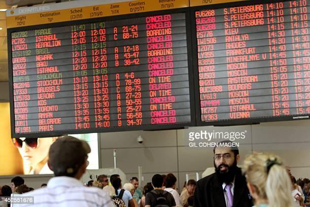 Israeli passengers walk near a departure time flight board displaying various cancellations at Ben Gurion International airport near Tel Aviv on July...