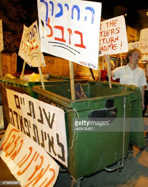 Israeli Peace Now activists hold up placards during a demonstration in front of Israeli Prime Minister Ariel Sharon's official residence in Jerusalem...