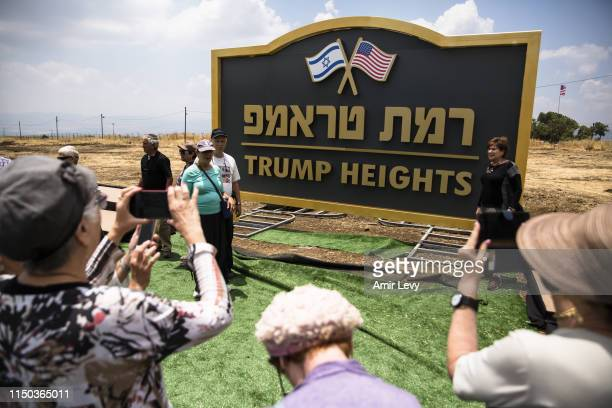 Israeli people take photos of a sign for a new settlement named after US President Donald Trump on June 17 2019 in Golan Heights Israel The Israeli...