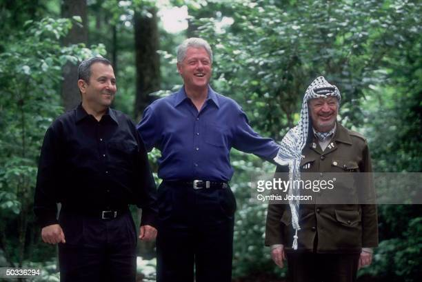 Israeli PM Ehud Barak, Pres. Bill Clinton & Palestinian leader Yasser Arafat strolling grounds of Camp David before getting down to business of...
