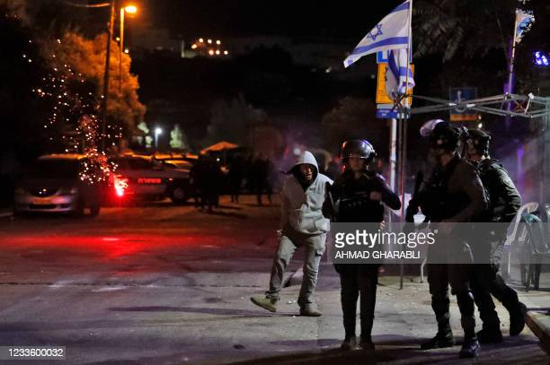 Israeli police and a settler react as Palestinians launch fire works near an Israeli settlers house in the Sheikh Jarrah neighbourhood of...
