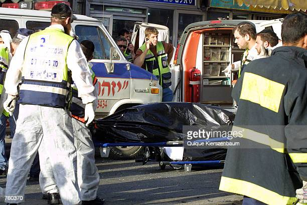 Israeli police and Orthodox Jews carry a body from the scene of a Palestinian suicide bomb attack at the Machane Iehuda market April 12 2002 in the...