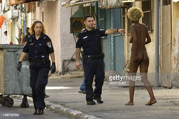 Israeli police approach an African prostitute near Levinsky Park in the Mediterranean city of Tel Aviv where thousands of migrants reside on June 12...