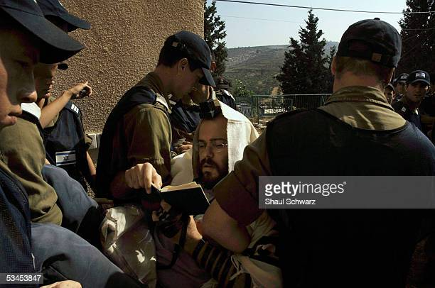 Israeli police carry away a rightwing settler activist wrapped in a Jewish prayer shawl during the evacuation August 23 2005 of Sanur settlement in...