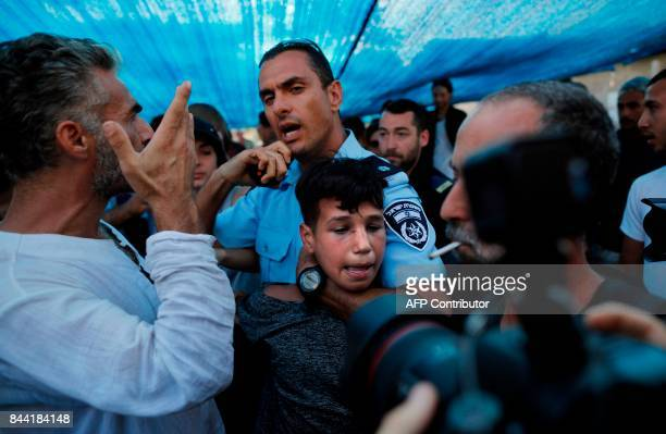 Israeli police detain a Palestinian boy on September 8 during a protest in front of the house seized by new Jewish owners in the Arab neighbourhood...