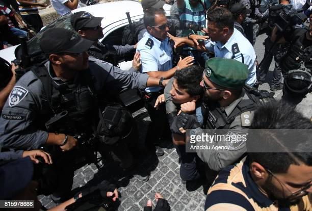 Israeli police detains a Palestinian as Palestinians perform night prayer in front of the new security metal detectors, outside one of the main...