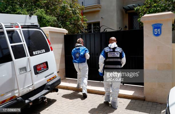 Israeli police forensics experts enter the gated house of the Chinese ambassador where he was found dead, in Herzliya on the outskirts of Tel Aviv,...