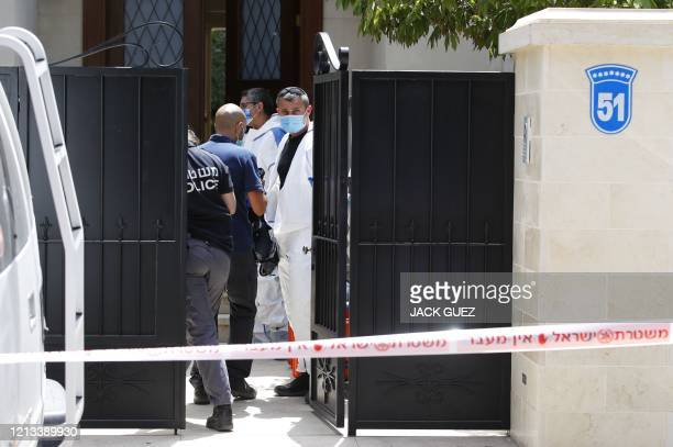 Israeli police officers and forensics experts enter the cordoned-off gated home of the Chinese ambassador where he was found dead, in Herzliya on the...
