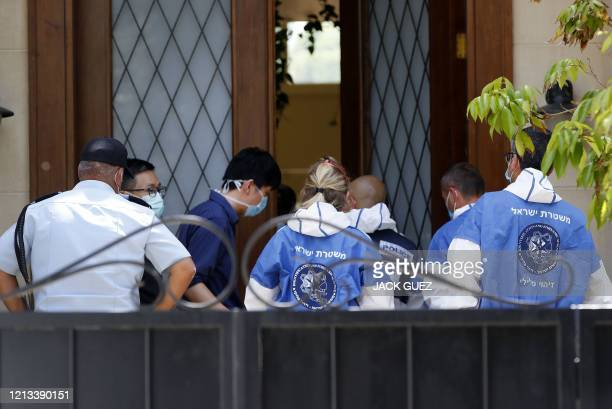 Israeli police officers and forensics experts talk to people at the gated house of the Chinese ambassador where he was found dead, in Herzliya on the...