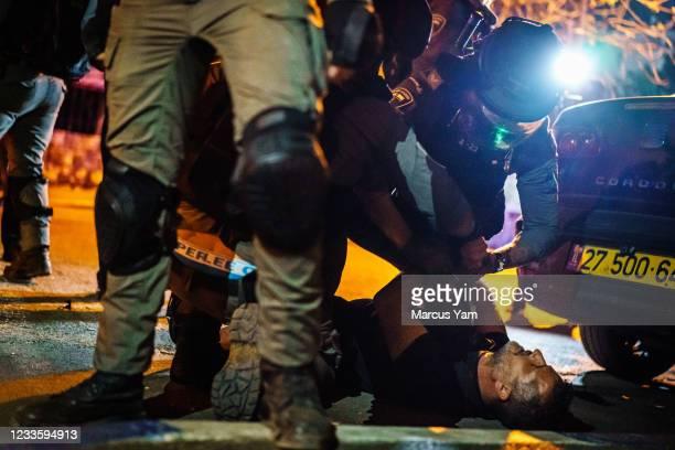 Israeli police officers detain a Palestinian man who was crossing the street in the Sheikh Jarrah neighborhood in Jerusalem, Israel, Monday, June 21,...