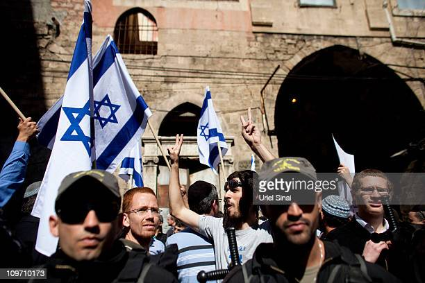 Israeli police officers guard right-wing activists as they wave their national flag during a right-wing activists protest against 'the Islamic take...