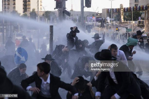 Israeli police officers intervene UltraOrthodox Jews with water cannons as they gather to protest against the forced military service policy of the...