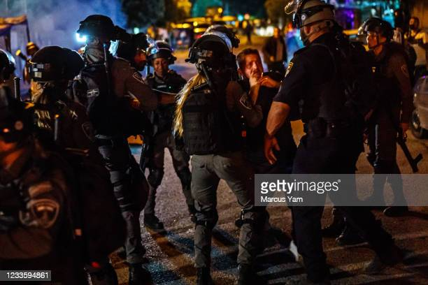 Israeli police officers outnumber and confront a Palestinian man who was crossing the street in the Sheikh Jarrah neighborhood in Jerusalem, Israel,...