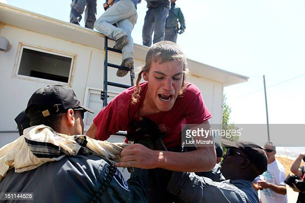 Israeli police officers pulls a Jewish settler down a ladder as he removes him from atop a structure on September 2 2012 in the illegal outpost of...