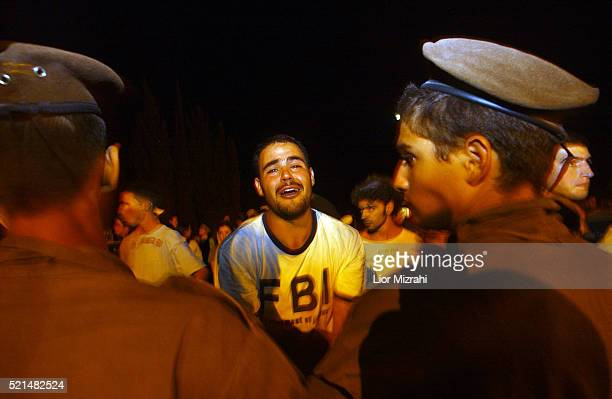 Israeli police officers scuffle with a Gush Katif resident in opposition of Ariel Sharon's scheduled pullout plan on Saturday July 16 2005 near the...
